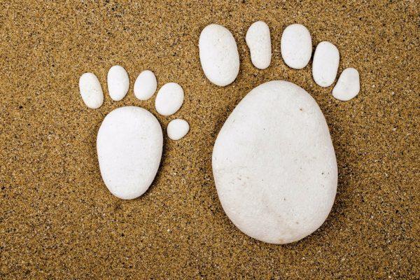 galets en forme de pieds sur sable